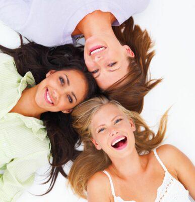 3 Frauen liegen auf dem Boden und lächeln in die Kamera