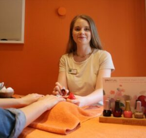 Kosmetikerin bei der Maniküre-Behandlung