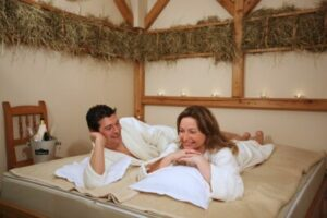 Paar in Bademänteln auf Behandlungsmatte
